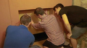 Three men solving a puzzle