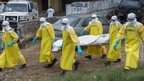 Liberian health care workers on an Ebola burial team collect the body of an Ebola victim at a motor vehicle garage in Paynesville on the outskirts of Monrovia, Liberia, 9 September 2014