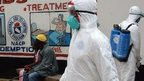 Liberian Red Cross health workers wearing protective suits arrive to carry a body of a victim of the Ebola virus on 12 September 2014 in a district of the capital, Monrovia