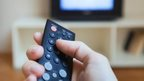 A person pressing a button on a television remote