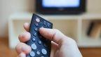 A person pressing a button on a television remote