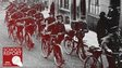 A line of world war one soldiers pushing bicycles along a street
