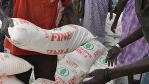 Men carry maize flour sacks during a food distribution by the Catholic Church to refugees and displaced people in Juba on 30 August 2014