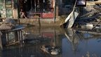 A shopkeeper looks at a flooded street in Srinagar. Photo: 16 September 2014
