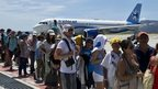 Tourists queue before boarding planes at Los Cabos international airport (16 September 2014)