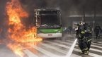 Fire fighters work to extinguish a bus on fire during clashes in Sao Paulo, Brazil,