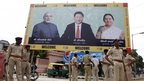 Indian policemen stand next to a welcome hoarding being erected ahead of an anticipated visit by Chinese President Xi Jinping as they review security arrangements in Ahmadabad, India, Monday, Sept. 15, 2014
