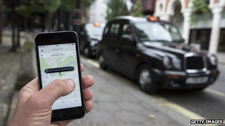 Uber app with black cab in background
