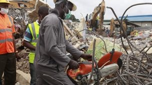 A rescue worker uses a chain saw as the search for survivors continues in the rubble of a collapsed building belonging to the Synagogue Church of All Nations in Lagos, Nigeria, Tuesday 16 September 2014