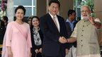 Chinese President Xi Jinping (C) accompanied with his wife Peng Liyuan (L), and Indian Prime Minister Narendra Modi as the two men shake hands in Ahmedabad, India, 17 September 2014.