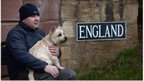 "A man and a dog sit next to a sign saying ""England"""