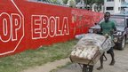 Vendor pushes bread past sign warning of Ebola risks