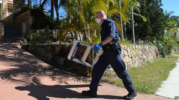 A police officer searches a house in Mount Gravatt, Brisbane (18 September 2014)