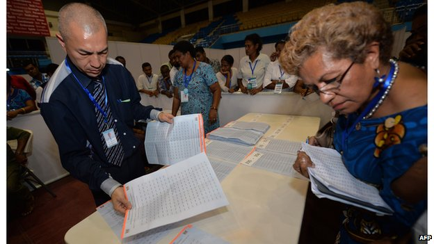 An election supervisor counts votes with scrutinisers looking on at a local sports arena after the poll booths closed in the Fiji elections in the capital Suva