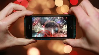 A person taking a photo of fireworks on a smartphone