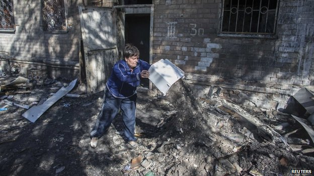 A woman clears up after shelling in Donetsk (17 Sept)