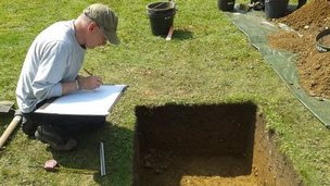 Archaeologist records details of an excavated pit