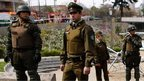 Police officers stand guard in an area where a bomb exploded in Santiago - 8 September 2014