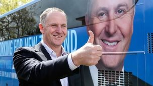 Prime Minister John Key gives the thumbs up outside his campaign bus during the National Party Bus Trip