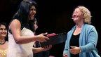 Dr. Sonal Saraiya, left, accepts the Ig Nobel Prize for Medicine from Nobel Laureate Carol Greider during a performance at the Ig Nobel Prize ceremony at Harvard University, in Cambridge, Mass.,Thursday, Sept. 18, 2014.