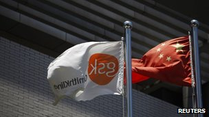 A flag bearing the logo of GlaxoSmithKline flutters next to a Chinese national flag outside a GSK office in  Shanghai