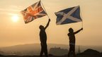 Two men holding flags aloft over Edinburgh - union jack and Saltire