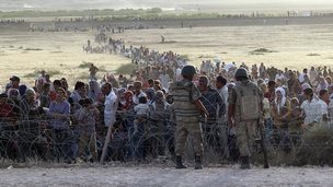 Turkish soldiers stand guard as Syrians wait behind the border fences. 18 Sept 2014
