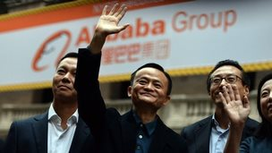 Jack Ma waves and smiles outside the New York stock exchange in front of an Alibaba sign