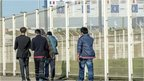 Migrants walk past the ferry terminal in Calais