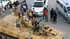 Islamic State fighters parade through the Syrian city of Raqqa in an armoured vehicle (30 June 2014)
