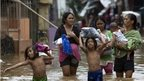 Locals walk through flood water in Cainta town, Philippines