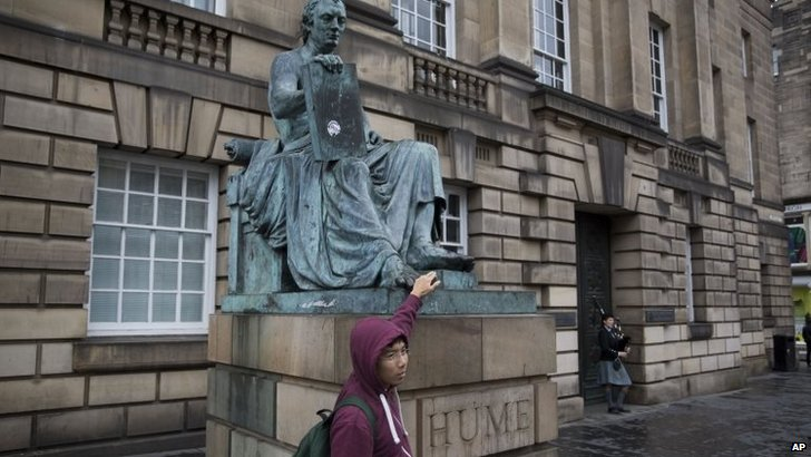 A tourist poses for a photograph with a statue of Scottish philosopher David Hume as a piper plays in the background in Edinburgh