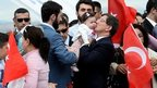 Turkish Prime Minister Ahmet Davutoglu celebrates with freed hostages in Ankara.
