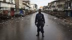 Police officer on deserted street in Freetown