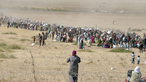 Syrian Kurds wait behind the border fence to cross into Turkey near the south-eastern town of Suruc in Sanliurfa province, 19 September 2014.