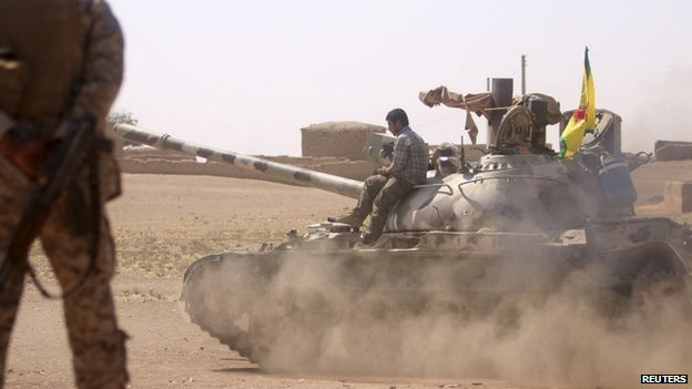 Kurdish People's Protection Units (YPG) drive a tank in villages surrounding Jazaa, in Qamishli countryside, after they seized control of the area from Islamic State fighters, on the Iraqi-Syrian border on 30 August 2014.