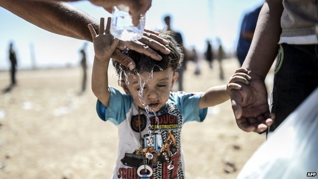 A Syrian Kurd pours water on a child after they crossed the border between Syria and Turkey near the south-eastern town of Suruc in Sanliurfa province, on 20 September 2014.
