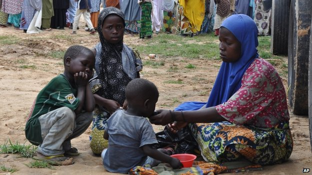 A woman and her children who fled their home following an attack by Islamist militants in Bama take refuge at a school in Maiduguri, Nigeria, on 9 September 2014