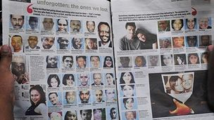 A man reads a newspaper with portraits of the Westgate victims