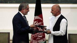 Abdullah Abdullah (left) and Ashraf Ghani exchange signed agreements. 21 Sept 2014