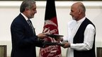 Abdullah Abdullah (left) and Ashraf Ghani exchange signed agreements. 21 Sept 2014