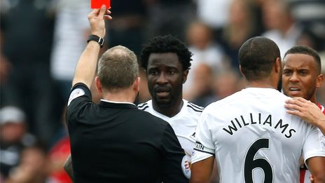 Swansea skipper Ashleigh Williams looks on as Wilfried Bony is shown the red card by referee Jonathan Moss