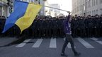A man with a Ukrainian flag walks past police during an anti-war rally in Moscow - 21 September 2014
