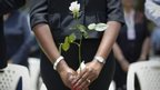 A woman holds a flower as she joins others in prayers at a memorial ceremony held in Nairobi, Kenya - 21 September 2014