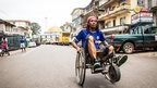 A man travels along a street in his wheelchair during a three-day lockdown to prevent the spread on the Ebola virus in Freetown, Sierra Leone, Sunday, Sept. 21, 2014