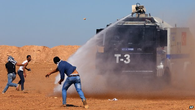 Turkish security forces use teargas and water cannons to disperse protesting local people as several hundred Syrian refugees wait at the border in Suruc, Turkey, Sunday, Sept. 21, 2014