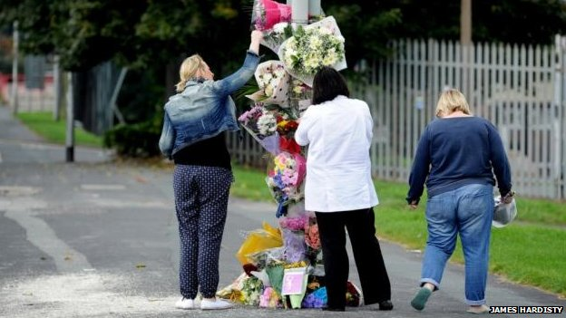 Women leaving bouquets on lamppost
