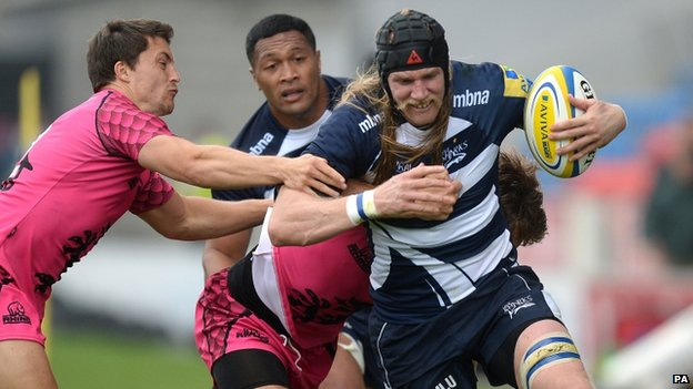 Sale Sharks' Magnus Lund is tackled by London Welsh's Nic Reynolds and Tristan Roberts (left)