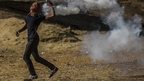 A Kurdish protestor throws a gas canister back to Turkish soldiers near the Syrian border after Turkish authorities temporarily closed the border near the south-eastern town of Suruc in Sanliurfa province (22 September 2014)
