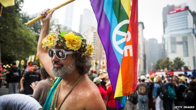 A shirtless man holds a peace flag during protests in New York City on 21 September, 2014.